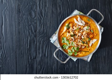 hearty spicy Mulligatawny soup with chicken meat and coconut milk sprinkled with fried cashew in a metal pot on a black wooden table,  Indian and english cuisine, view from above, flatlay