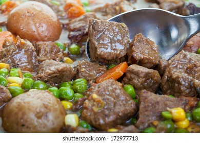 Hearty and traditional beef stew close up, focus on the spoon.