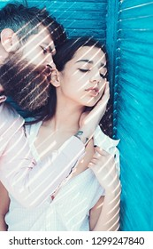 Heat concept. Couple chilling near jalousie, stripes of sunlight and shadow on faces. Girl in unbuttoned shirt and man with beard. Couple in love on calm faces near turquoise jalousie