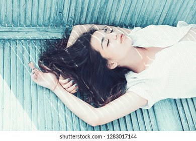 Heat concept. Woman brunette chilling while stands near jalousie, stripes of sunlight and shadow on her face. Lady wears unbuttoned shirt. Girl on calm face lean on turquoise jalousie