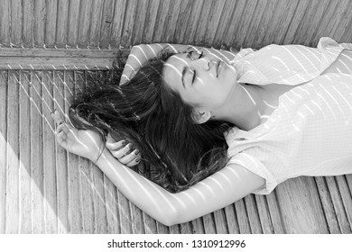 Heat concept. Woman brunette chilling while stands near jalousie, stripes of sunlight and shadow on her face. Lady wears unbuttoned shirt. Girl on calm face lean on turquoise jalousie.
