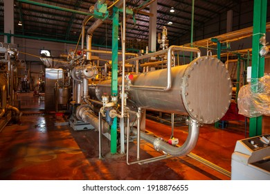 Heat exchanger at insulation in process area of pipeline flowing shiny stainless chemical in factory.