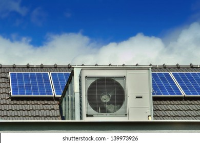 Heat Pump and Solar Panels on a Family House Roof