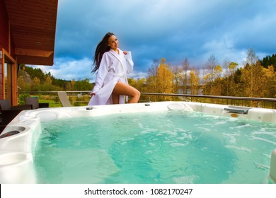 Heated swimming pool. The girl tunes the temperature of the pool. Hydromassage. A girl in a white bathrobe wants to take water treatments. Relax and relax in the hot tub.