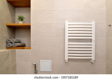 Heated towel rail and a niche with shelves in a modern bathroom. Ecominimalism