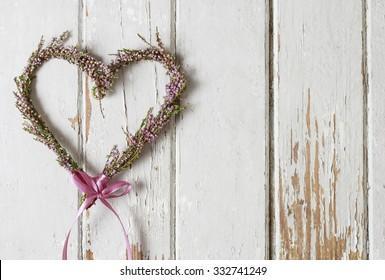 Heather (erica) door wreath in heart shape on wooden background, copy space