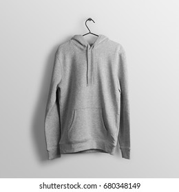 Heather grey blank hoodie mockup on hanger, hanging against empty wall background.