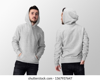 Heather grey blank hoodie on a young middle eastern man in jeans, isolated on a white studio background, front and back view mockup of heather grey hoodie with place for your logo or design