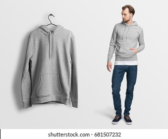 Heather grey hoodie on a man in jeans, isolated, mockup. Hanging hoodie, against empty wall background.