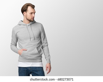Heather grey hoodie on a young man in jeans, isolated, with copy space, mockup.