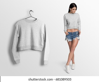 Heather grey long sleeve crop top on a young woman in shorts,isolated, mockup. Crop top mockup on hanger, hanging against empty wall background.