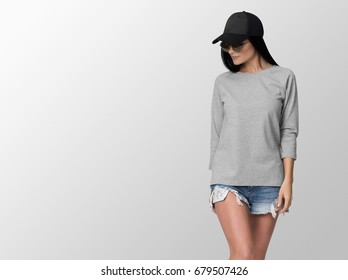 Heather grey long sleeve t-shirt on a young woman in shorts and cap, isolated, with copy space, mockup.