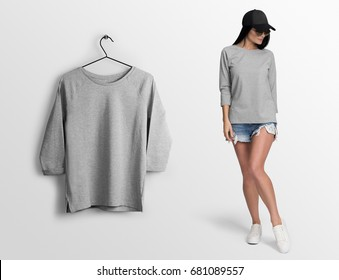 Heather grey long sleeve t-shirt on a young woman in shorts, sunglasses and baseball hat, isolated mockup. Hanging t-shirt long sleeves, against empty wall.