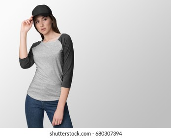Heather grey pullover, long sleeve baseball t-shirt on a young woman in jeans and baseball cap, isolated, with copy space, mockup.