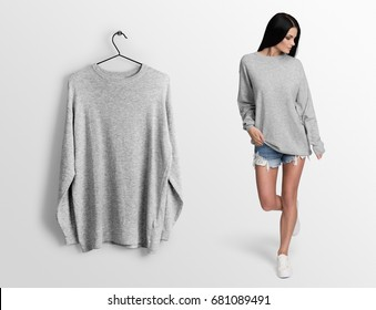 Heather grey pullover, long sleeve t-shirt on a young woman in shorts, isolated,mockup. Pullover, hoodie mockup on hanger, hanging against empty wall background.