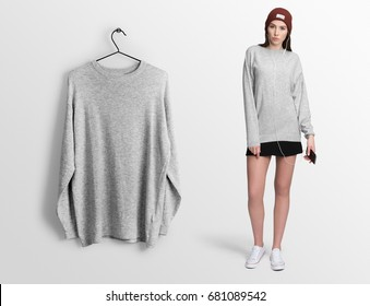 Heather grey pullover, long sleeve t-shirt on a young woman in skirt, holding a smartphone isolated, mockup. Pullover, hoodie mockup on hanger, hanging against empty wall background.