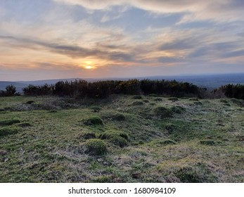 Heather-like flora marks the horizon, behind which the sun attempts to set. The grass is lumpen and harsh and the sky overcast and moody.