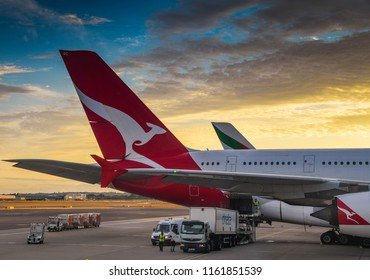HEATHROW AIRPORT, LONDON - JULY 2018: Freight being loaded into a Qantas Airbus A380 at sunset at London Heathrow Airport.