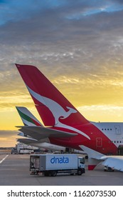 HEATHROW AIRPORT, LONDON - JULY 2018: Tail fin of a Qantas Airbus A380 airliner as the sun sets at London Heathrow Airport. An air freight lorry has stopped beneath it.