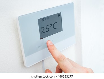 Heating concept. Hand is adjusting temperature in room on digital central thermostat control.