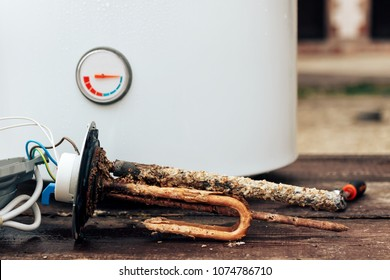heating element, rust and scale on boiler background, lying on wooden table.