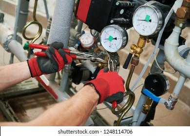 heating engineer or plumber in boiler room installing pipeline manometer