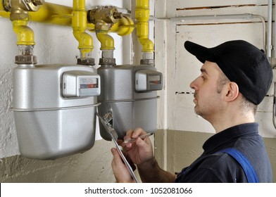 Heating fitter checks gas consumption at gas pipe and meter counter