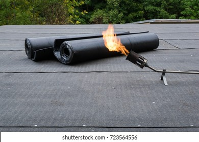 Heating and melting bitumen roofing felt Flat roof installation.