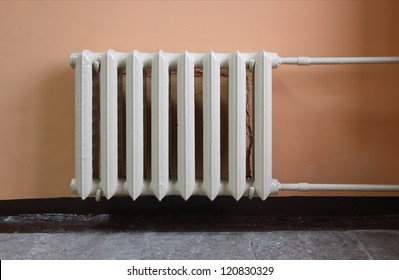 Heating radiator on pink wall in a room.