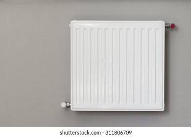 Heating radiator with thermostat. Connection is done through the wall