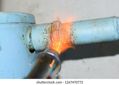 Heating a steel pipe with a blowtorch. The flame of a blowtorch.