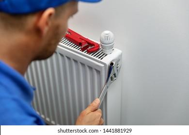 heating system installation and maintenance service. plumber installing radiator