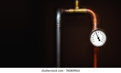 Heating system's cooper pipe and steel pipe with Thermometer on a copper pipe. On a dark background. Close up. Space for text.