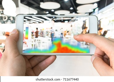 Heatmap Analytic in smart retail shop technology concept. Hand using smart phone with Pheat sense application check shoppers passed from any point in store.