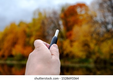 Heat-not-burn tobacco product technology. Modern heating system of tobacco in the hand of a man on a blurred background of autumn landscape. Selective focus.