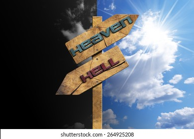Heaven and Hell - Sign on Blue Sky. Wooden directional sign with two arrows in opposite direction with text heaven and hell on blue and black sky with clouds and sun rays