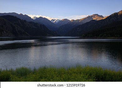 Heavenly Lake of Tianshan (Tianchi) - Alpine lake in Xinjiang Province, China. Part of the Chinese Tian Shan mountains, beautiful crescent shaped lake. Also known as the Pearl of Heavenly Mountain.
