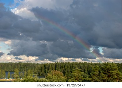 Heavenly landscape. Rainbow in a stormy sky over a forest