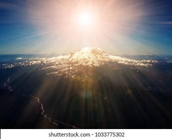 Heavenly rays of sunlight above mountain peak