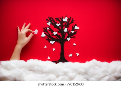 A heavenly scene in passion red with a woman's hand holding a heart from a love tree. Cotton clouds and falling small hearts hand manufactured on a red paper background.
