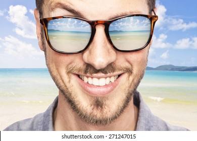 heavenly tropical destination reflected in young beautiful man's sunglasses. joyful portrait