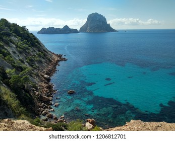 Heavenly view from the blue crystalline sea of Cala D'Hort where the island of Es Vedra stands out in all its splendor