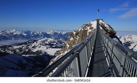 Heavenly winter walk. Winter scene in the Swiss Alps. Suspension bridge connecting two mountain peaks on 3000m altitude. View from the Glacier des Diablerets ski area.