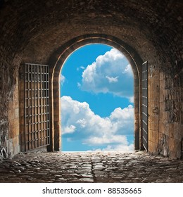 Heaven's gate. Dark tunnel corridor with arch opening to a beautiful cloudy sky. Light at the end of the tunnel.