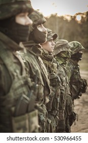 Heavily armed soldiers in battle dress uniform standing in a row outdoor