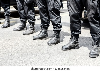 Heavily armored special police forces create barricade on the street. Close up of boots. Tactical armed policeman on protest. Intervention unit. Riot police team in black uniform. Demonstration