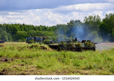 A heavily armoured tank or transporter truck riding along the battlefield generating some smoke with two other military vans in the background seen on a cloudy summer day near a dense forest or moor