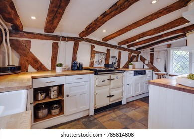 Heavily beamed kitchen within a 16th Century English cottage fitted with traditional style cupboards, drawers, stove and hob with oak counter-tops and utentils hanging on the wall
