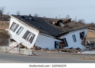 A heavily damaged, collapsing house. The second floor has fallen into the first, and debris is around the building.