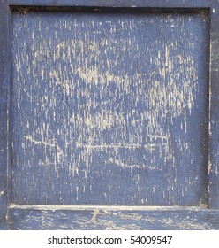 heavily damaged scratched piece of dark blue painted wood